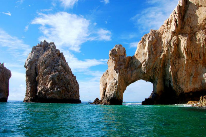 Escape Case Team Building, Cabo San Lucas Escape the Case. A bright blue sky with sparse clouds looms over the rocky cliffs and emerald water below. The feet of a natural stone arch are stained dark brown from the receding tide, and the whole between them is large enough for a ship to pass through.