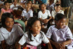 Estudiantes sonrientes se sientan en un aula de la escuela primaria Bislig en la ciudad de Tanauan, provincia de Leyte, Filipinas.