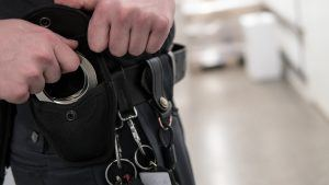 Police officer or security staff takes up handcuffs for arrest of criminal.