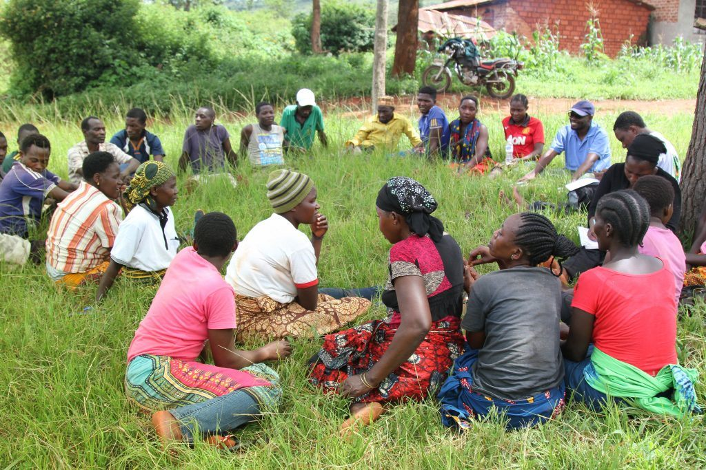 Group of people gathered in the grass in a circle participating in a group discussion in Tanzania.